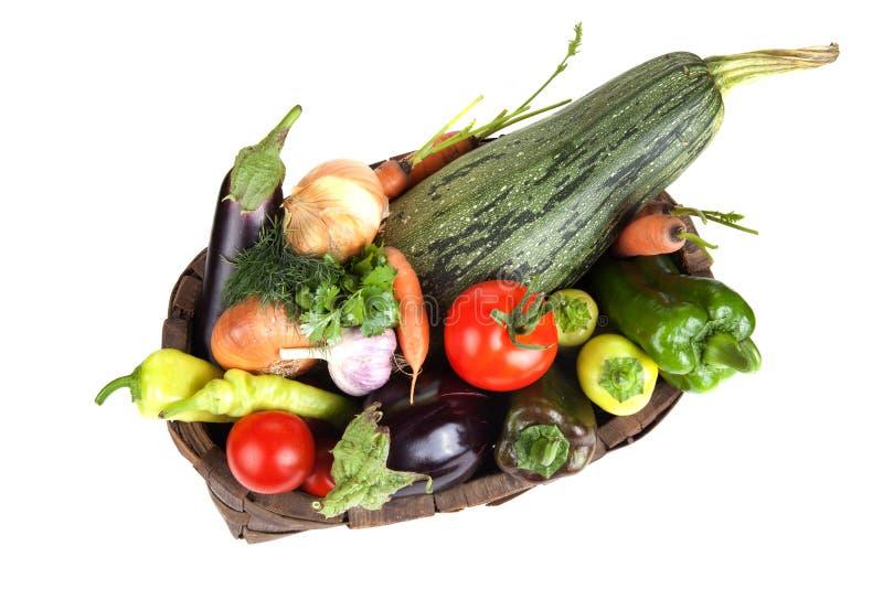 Geassorteerde groenten in een oude houten die mand op witte bedelaars wordt geïsoleerd stock foto's