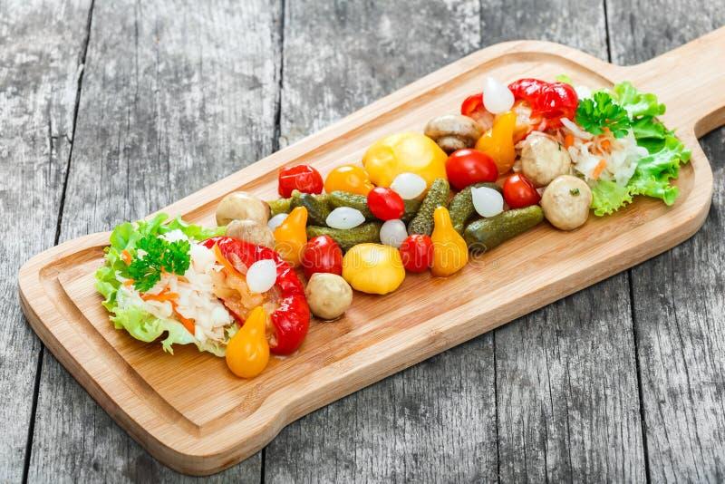Geassorteerde groenten in het zuur - Zuurkoolkool, peper, komkommers, tomaten, uien, paddestoelen en kruiden op scherpe raad royalty-vrije stock afbeeldingen