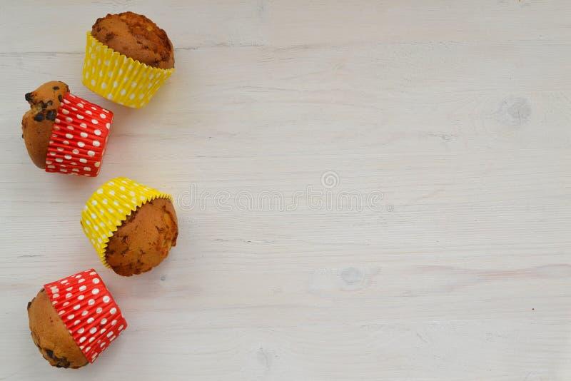 Geassorteerde heldere gekleurde decoratieve cupcakes op sjofele houten achtergrond met exemplaarruimte stock foto