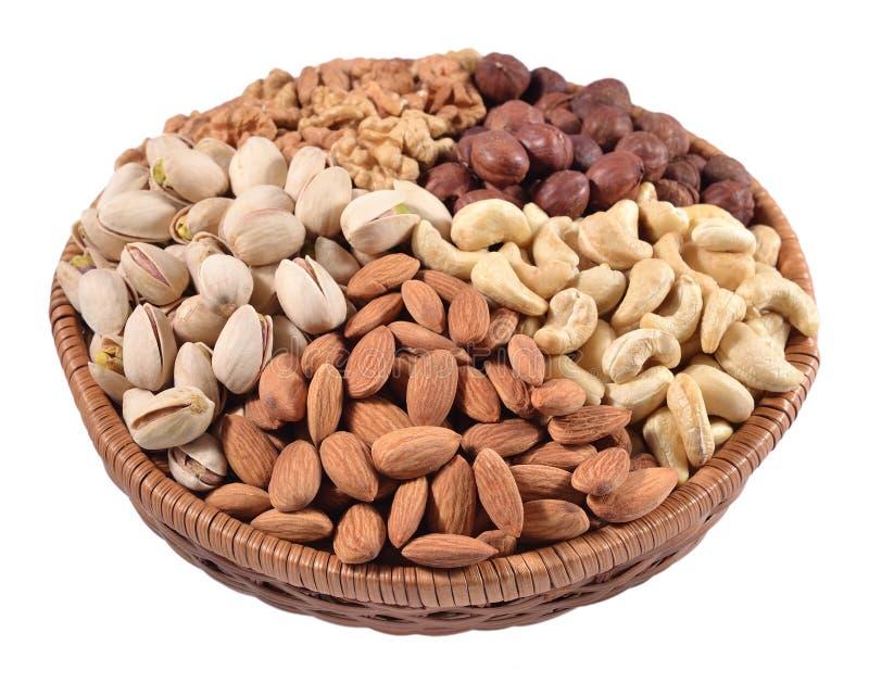 Geassorteerde noten in een rieten kom op een witte achtergrond royalty-vrije stock afbeeldingen