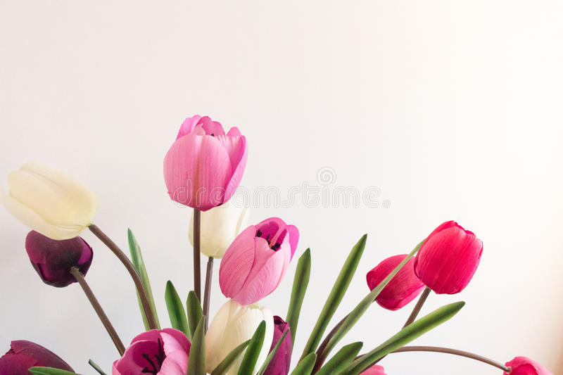 Geassorteerde plastic kunstmatige tulpenbloemen die in roze vals zijn royalty-vrije stock fotografie