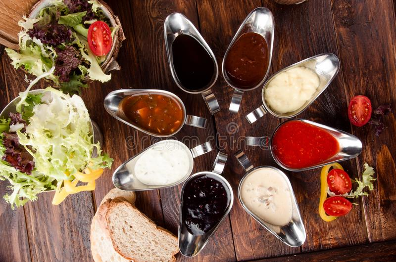 Geassorteerde sausen: ketchup, perigueux, minste, sojasaus, pesto, bessensaus, bechamel in mooie aluminiumjuskommen stock foto