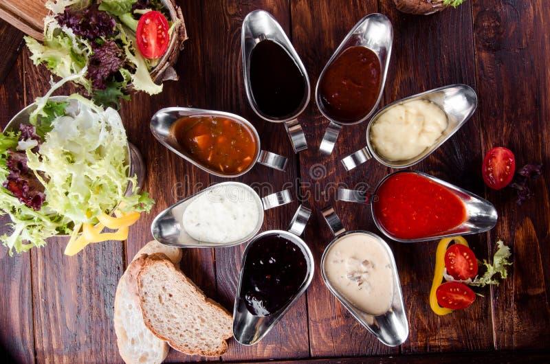 Geassorteerde sausen: ketchup, perigueux, minste, sojasaus, pesto, bessensaus, bechamel in mooie aluminiumjuskommen stock fotografie