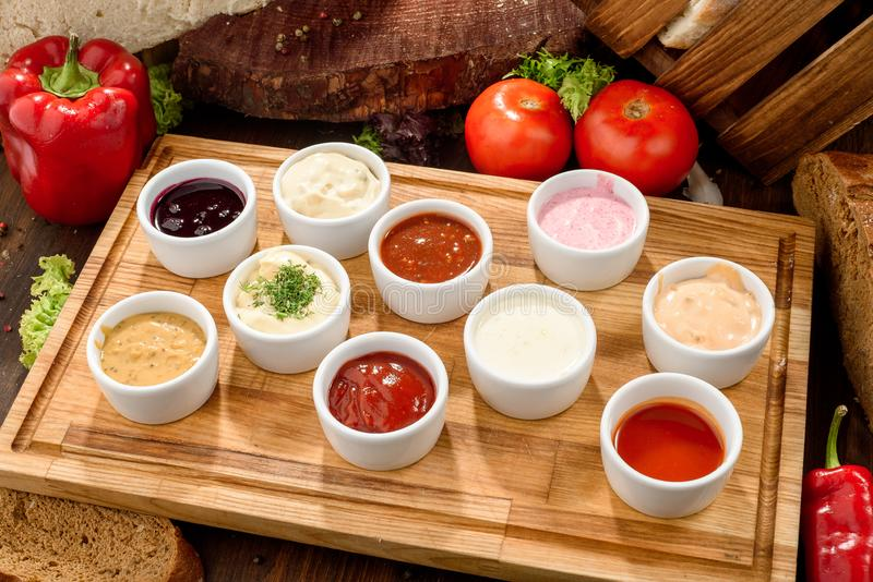 Geassorteerde sausen: ketchup, perigueux, minste, sojasaus, pesto, bessensaus, bechamel in witte sausboten stock foto