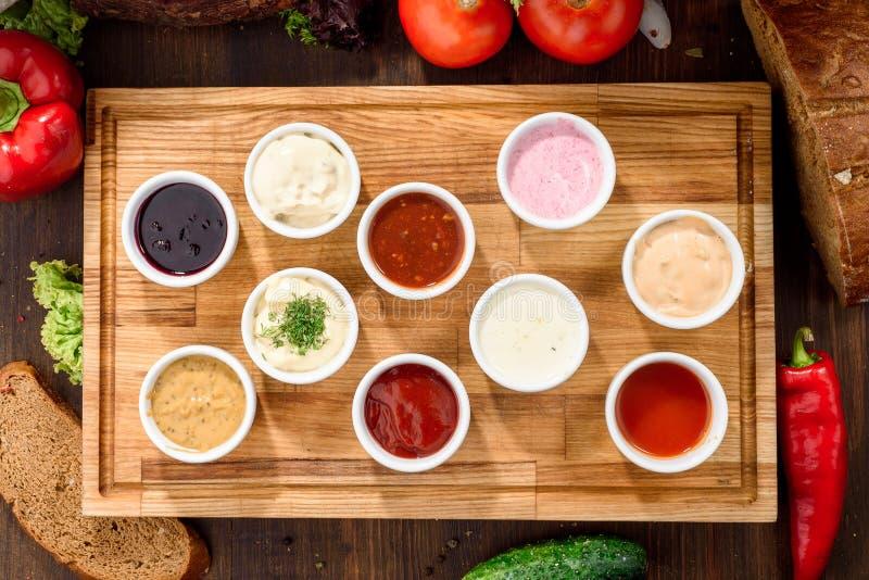 Geassorteerde sausen: ketchup, perigueux, minste, sojasaus, pesto, bessensaus, bechamel in witte sausboten royalty-vrije stock afbeelding