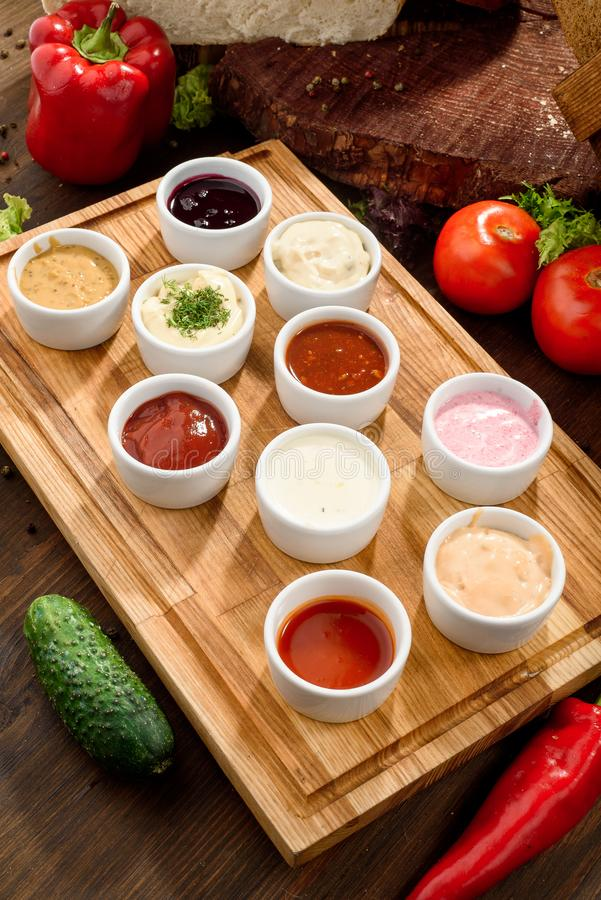 Geassorteerde sausen: ketchup, perigueux, minste, sojasaus, pesto, bessensaus, bechamel in witte sausboten royalty-vrije stock fotografie