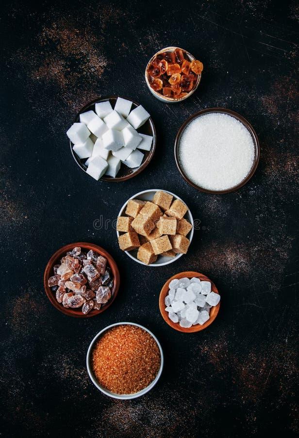 Geassorteerde verschillende types van suiker in kommen op een lijst aangaande een donkere achtergrond, verticaal beeld royalty-vrije stock foto's