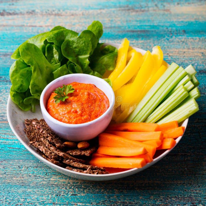 Geassorteerde verse groenten met onderdompeling Het gezonde Eten Geroosterde uitgespreide pepersaus, Houten achtergrond stock afbeeldingen