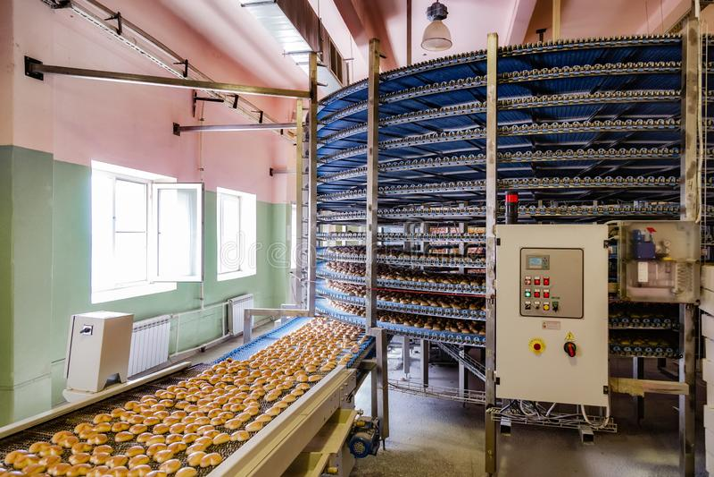 Geautomatiseerd om transportbandmachine in de fabriek, de koekjes en de cakesproductielijn van het bakkerijvoedsel royalty-vrije stock afbeeldingen
