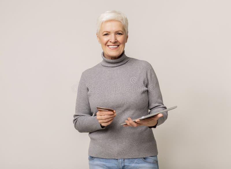 Geavanceerde vrouw die online winkelt met tablet en creditcard stock fotografie