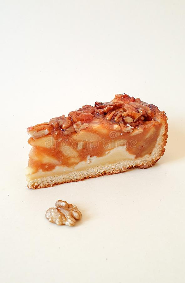 Gebäck Apfelkuchen mit Pecans, Karamel und halber Nuss auf hellem Hintergrund stockbilder
