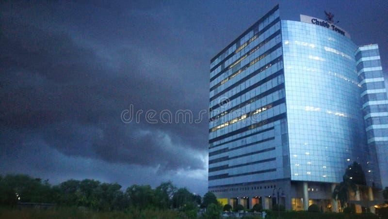Gebäude wird durch blaues Glas mit dunklem Regenwolkenhintergrund bedeckt lizenzfreie stockfotos