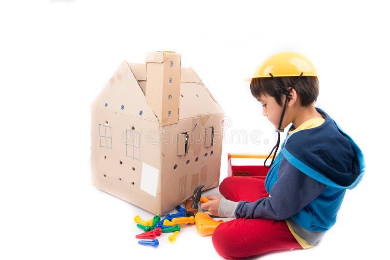 Gebäudepapierhaus durch kleinen Mechanikerjungen lizenzfreies stockfoto