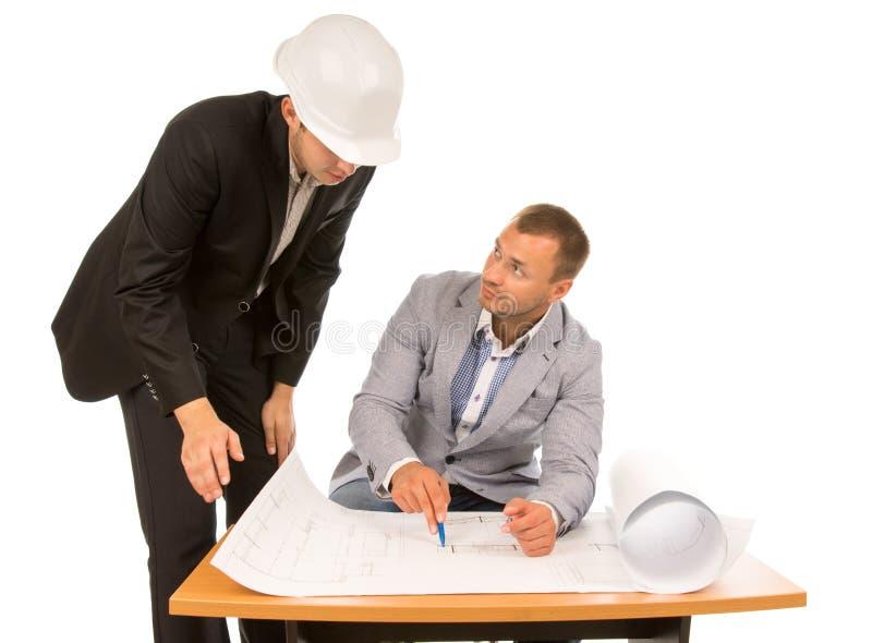 Gebäudevorarbeiter und -architekt, die einen Plan besprechen lizenzfreie stockfotografie