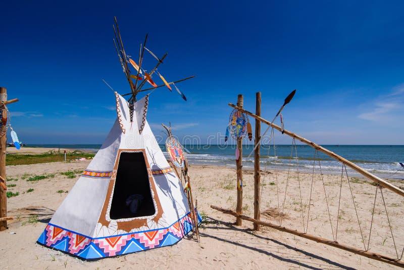 Gebürtiger indianischer Tipi und Totempfahl auf dem Strand blaue SK lizenzfreie stockfotografie