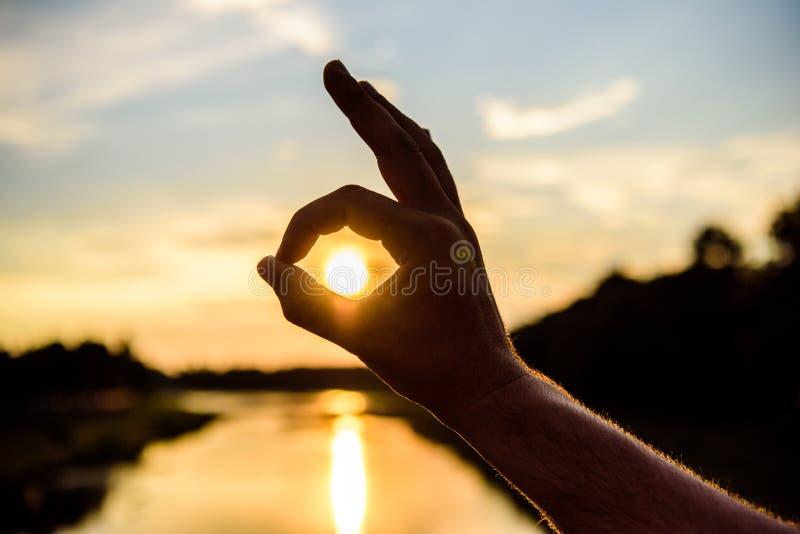 Gebaar van de silhouet het o.k. hand voor zonsondergang boven rivierwaterspiegel De romantische atmosfeer van het zonsondergangzo stock afbeelding