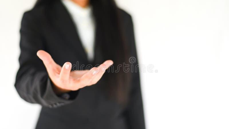 Gebaar van het bedrijfs toont het lege handwerkstuk uit rek - de bedrijfsvrouw in kostuum toont gebruikshand om iets op wit te ho stock fotografie