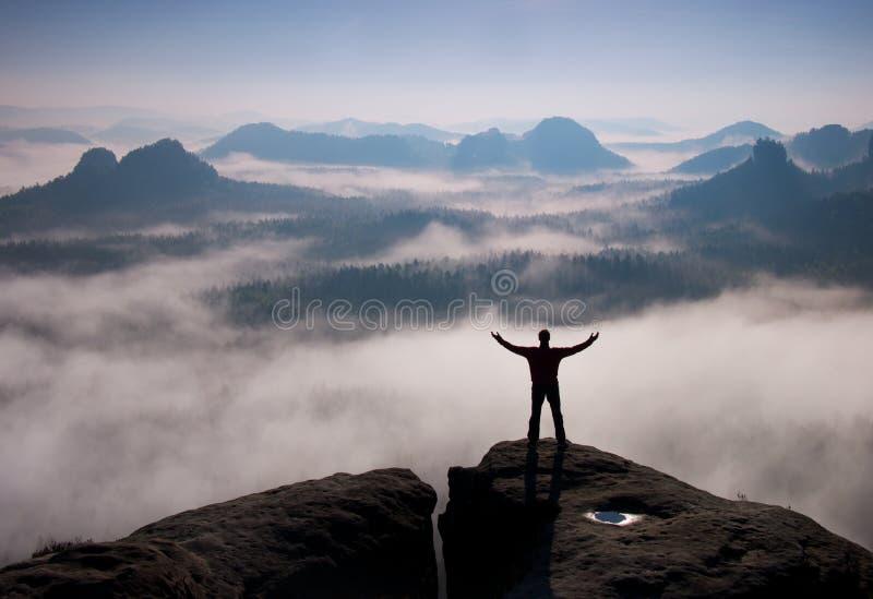 Gebaar van triomf Gelukkige wandelaar in zwarte Lange mens op de piek van zandsteenrots in nationaal park Saksen Zwitserland bove royalty-vrije stock afbeelding
