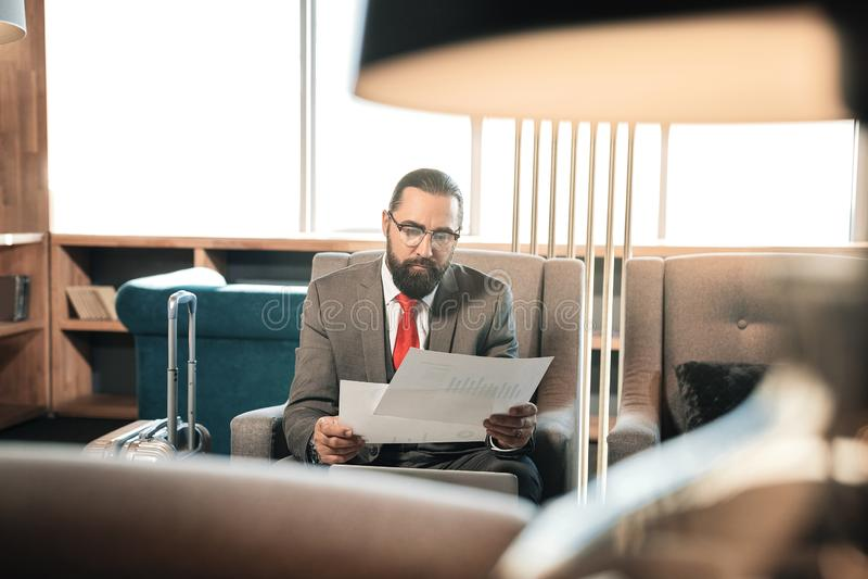 Gebaard donker-haired rijp van de bedrijfs zakenmanlezing contract stock fotografie