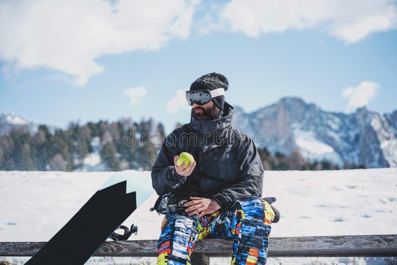 Gebaard snowboarded in sunglassmasker, bij de skitoevlucht op de achtergrond van bergen en blauwe hemel Mens die rust nemen en stock fotografie