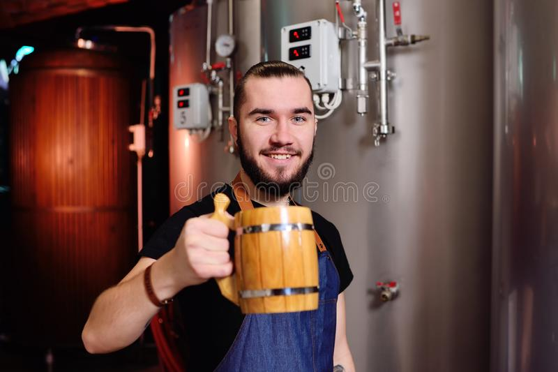 Gebaarde aantrekkelijke mannelijke brouwer met houten biermok ter beschikking op achtergrond van brouwerij stock afbeeldingen