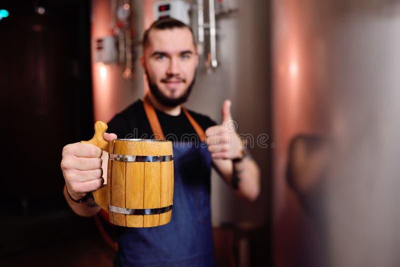 Gebaarde aantrekkelijke mannelijke brouwer met houten biermok ter beschikking op achtergrond van brouwerij royalty-vrije stock afbeeldingen