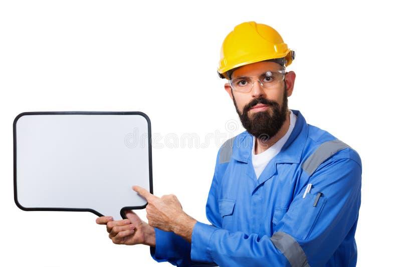 Gebaarde arbeider die in beschermende bouwhelm aan het witte schoolbord met geïsoleerde copyspace richten, stock fotografie