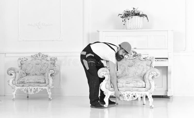 Gebaarde arbeider die zware retro leunstoel proberen op te heffen De verpakking van het meubilair en het bewegen zich aan nieuwe  royalty-vrije stock foto