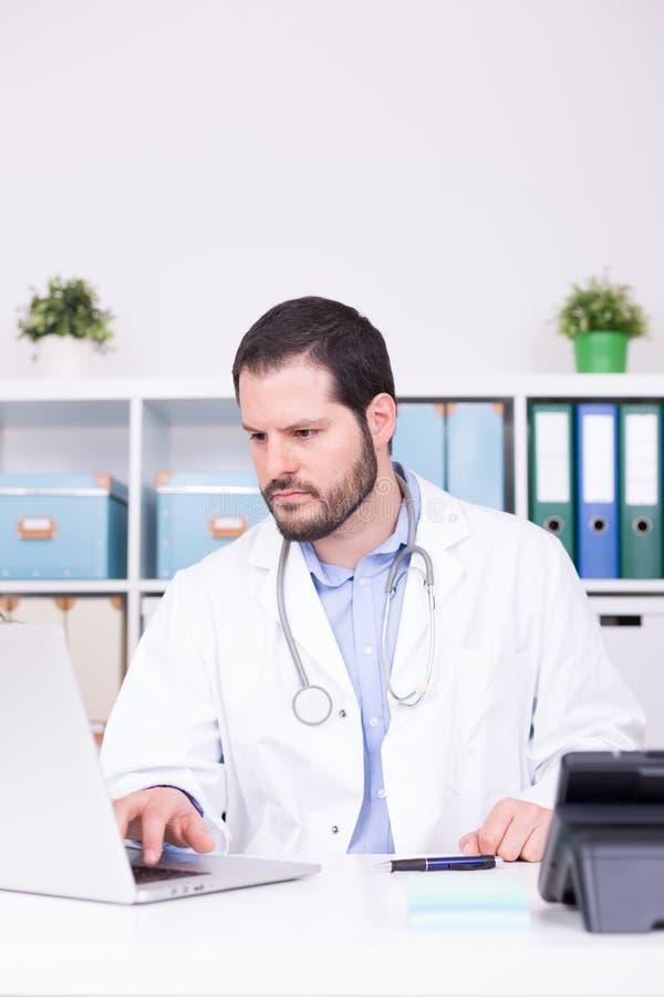 Gebaarde arts die op zijn kantoor werken Zaken en medisch concept stock foto