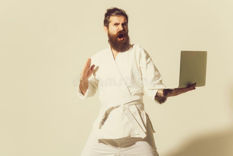 Gebaarde boze karatemens in kimono met laptop stock foto's