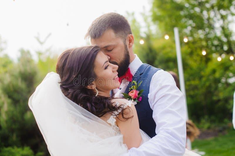 Gebaarde bruidegom die zijn bruidwang kussen openlucht royalty-vrije stock afbeeldingen