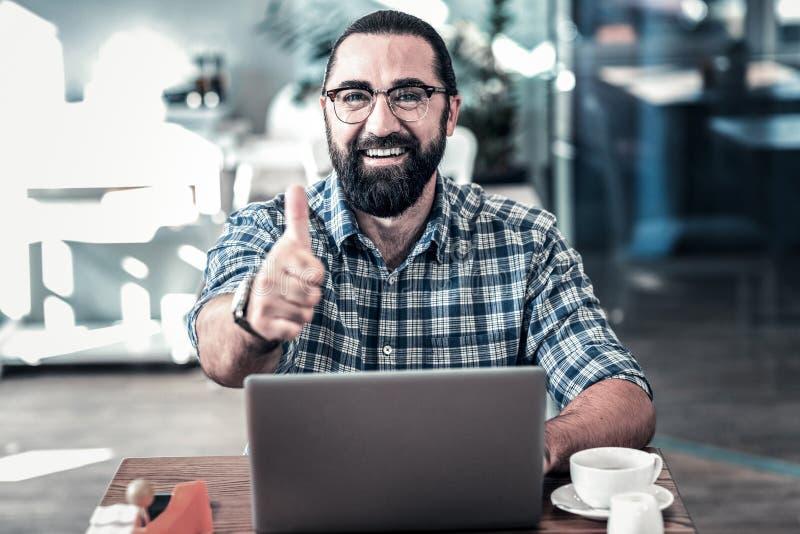 Gebaarde donker-eyed zakenman die het werk van zijn werknemers goedkeuren stock afbeelding