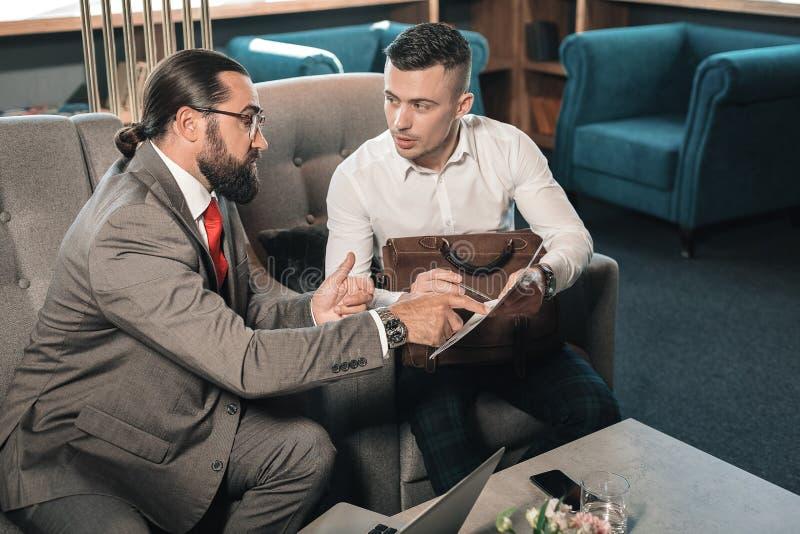 Gebaarde donker-haired partner die zijn advies over de situatie geven royalty-vrije stock afbeelding