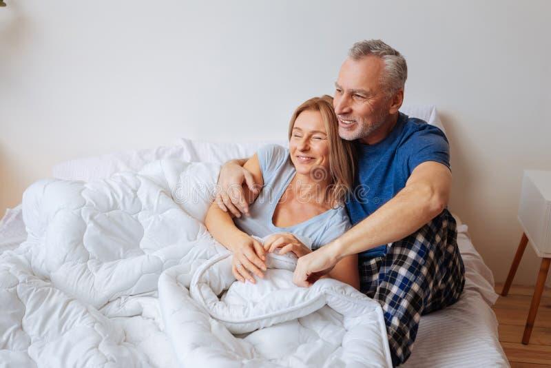 Gebaarde echtgenoot die pyjama's dragen die zijn mooie vrouw koesteren royalty-vrije stock fotografie