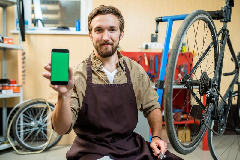 Gebaarde Fietswerktuigkundige met Smartphone royalty-vrije stock afbeeldingen