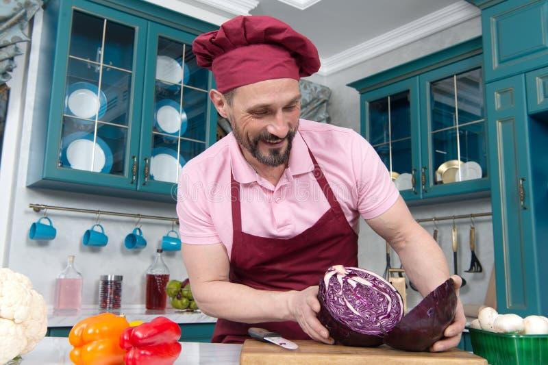 Gebaarde geglimlachte chef-kokgreep twee delen van rode kool bij keuken De kok sneed rode kool voor twee delen stock afbeeldingen