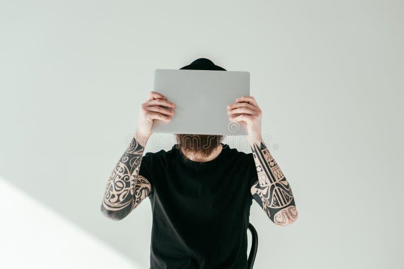 gebaarde getatoeeerde mens die gezicht behandelen met laptop royalty-vrije stock afbeelding
