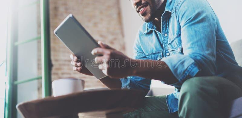 Gebaarde glimlachende Afrikaanse mens die tablet voor videogesprek gebruiken terwijl het ontspannen op bank in modern bureau Conc stock foto