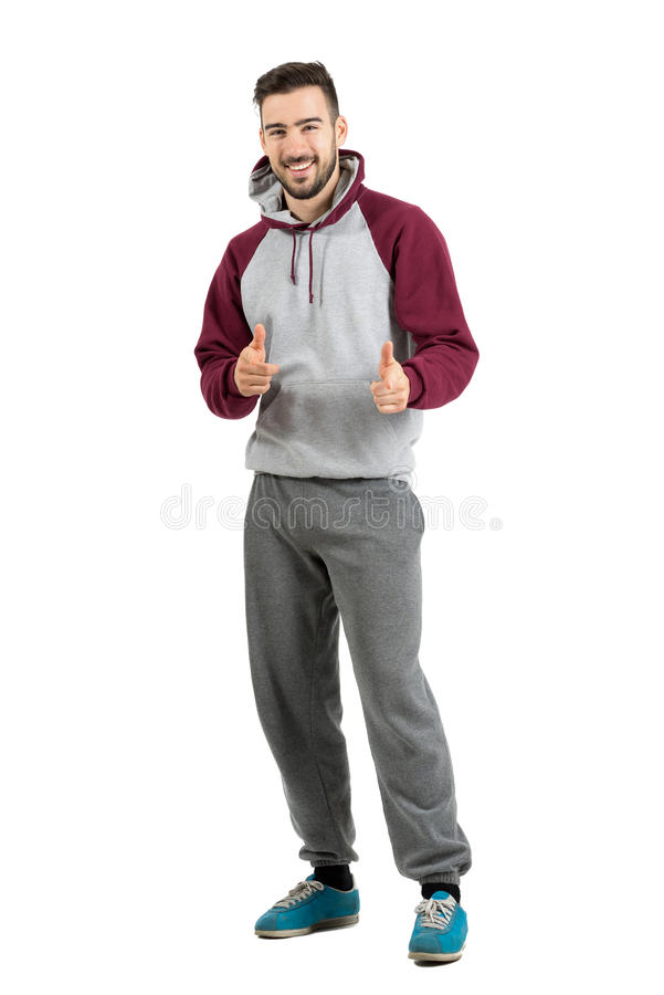 Gebaarde glimlachende jonge mens die in toevallige sportkleding de handgebaar richten van het vingerkanon op camera stock foto's
