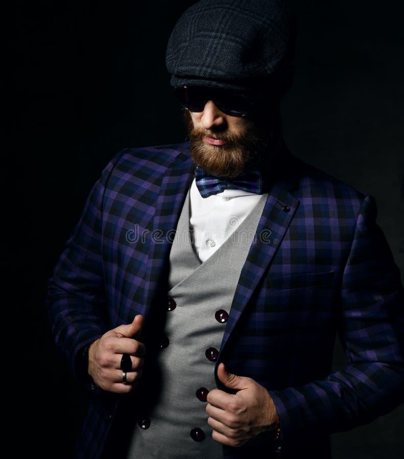 Gebaarde heer in plaidjasje, plaidvlinderdas, vest en ronde sunglelooks bij de vloer royalty-vrije stock fotografie