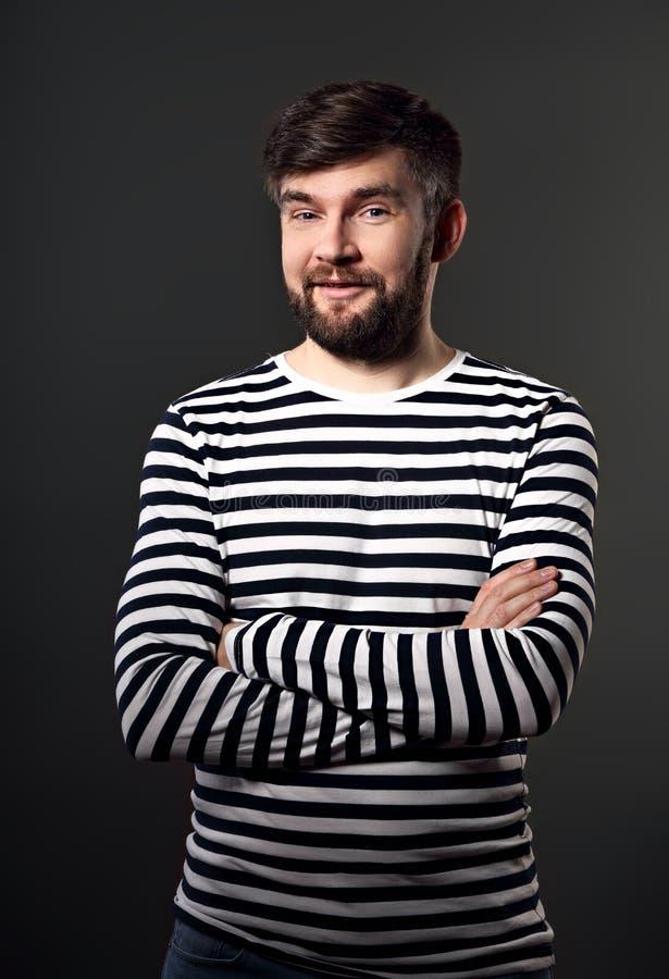Gebaarde het verrassen gelukkige emotionele mens met gevouwen wapens op grijs stock foto's