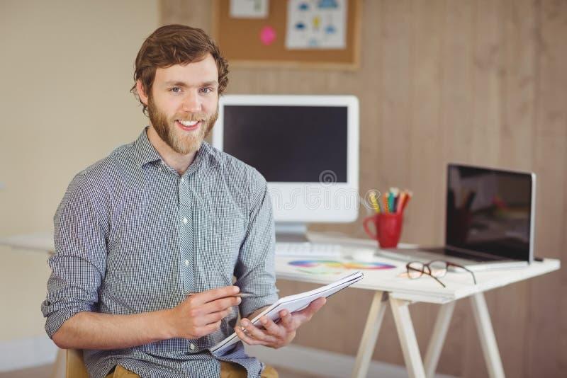 Gebaarde hipster die bij de nota's van de cameraholding glimlachen stock afbeelding