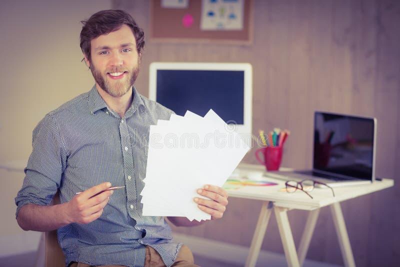 Gebaarde hipster die bij de nota's van de cameraholding glimlachen royalty-vrije stock foto