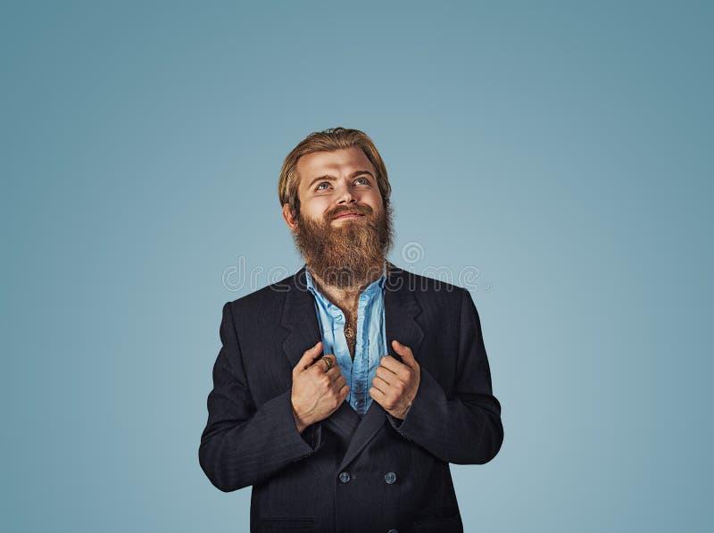 Gebaarde hipstermens die zijn hoofd die omhoog glimlachend kijken toenemen stock foto