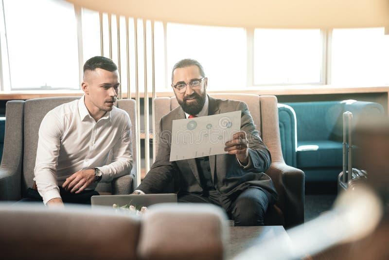 Gebaarde investeerder die glazen dragen die dichtbij zijn jonge stagiair zitten stock foto's