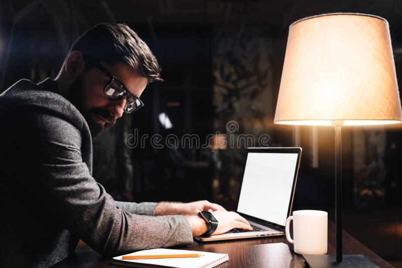Gebaarde jonge medewerker die glazen dragen die tekst op eigentijdse laptop in modern zolderbureau typen bij nacht De bedrijfsmen stock afbeelding