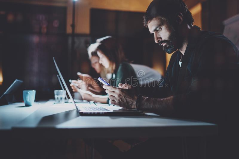 Gebaarde jonge medewerker die op nachtkantoor werken Mens die eigentijdse laptop en moderne smartphone gebruiken horizontaal vaag royalty-vrije stock foto's