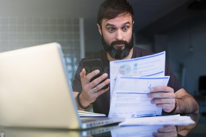 Gebaarde jonge mens die met laptop werken die thuis documenten doorbladeren Zakenman die door administratie thuis bureau gaan royalty-vrije stock afbeelding