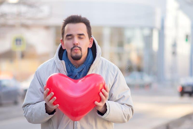 Gebaarde jonge mens met gesloten ogen en klaar om het houden van een rode de luchtimpuls van de hartvorm in de stad te kussen ste stock foto's