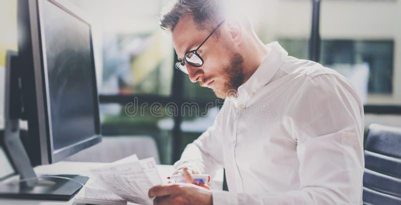 Gebaarde jonge zakenman die op modern kantoor werken Mens die wit overhemd dragen en nota's over de documenten maken panoramisch stock foto